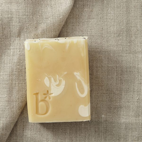 Pale yellow natural grapefruit soap above its white rectangular box laid on a brown material