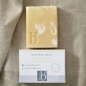 Yellow and white rectangular natural grapefruit soap laying on a brown material background above its white rectangular box