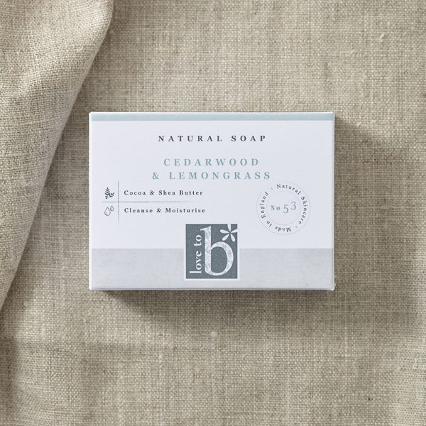 Natural cedarwood and lemongrass soap in its white rectangular box on a background of brown material