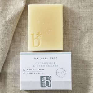 Creamy yellow natural cedarwood and lemongrass soap above its white rectangular box on a brown material background