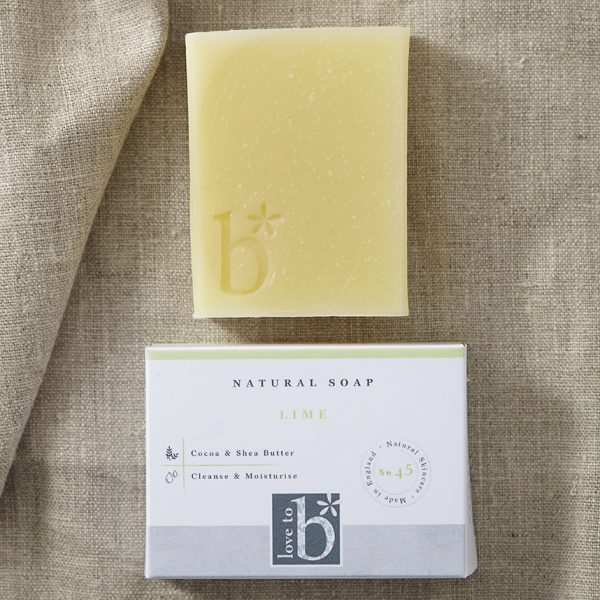 Pale yellow natural lime soap above its white rectangular box laid on a brown material