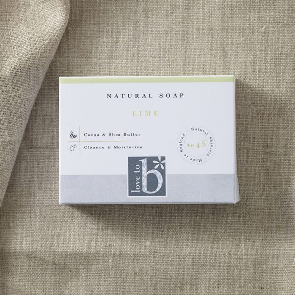 White rectangular natural grapefruit soap box laying on a brown material background