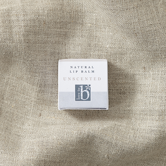 White square natural unscented lip balm box on a brown material background.