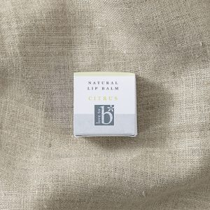 White square natural citrus lip balm box laid on a brown material