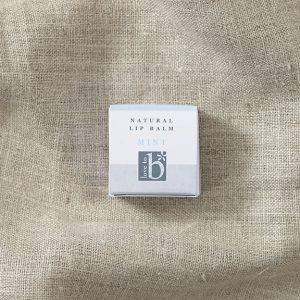 Square white natural mint lip balm box laid on a brown material