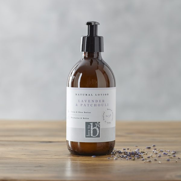 Natural lavender and patchouli lotion in an amber glass bottle with a white label next to some lavender buds on a wooden surface