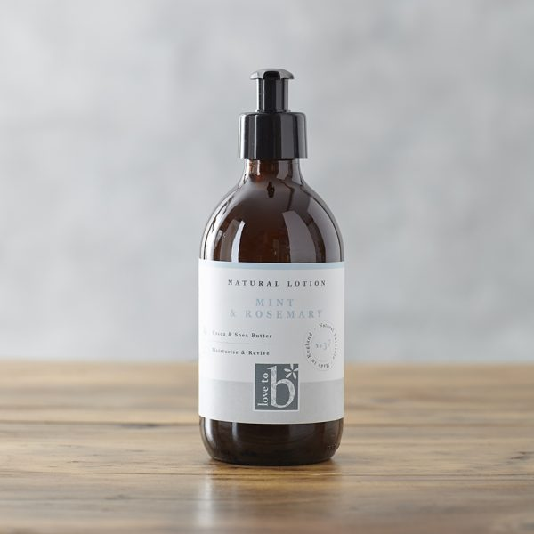 Natural mint and rosemary lotion in an amber glass bottle with a white label stood on a wooden surface