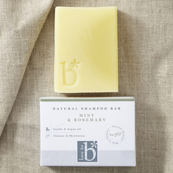 Creamy yellow natural mint and rosemary shampoo bar above its white rectangular box on a brown material background