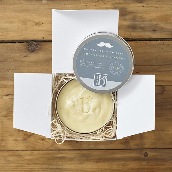 Creamy natural shaving soap in a metal tin with lid placed in a white square box on a wooden background
