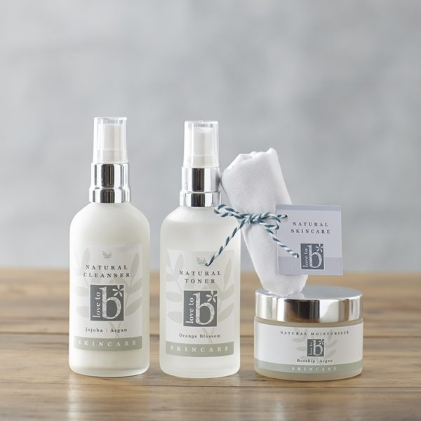 The full natural skincare gift box collection of cleanser, toner, moisturiser packaged in frosted glass with a muslin cloth on a wooden surface