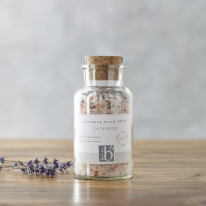 A glass bottle of natural lavender bath salts with a cork stopper and white label stood on a wooden surface