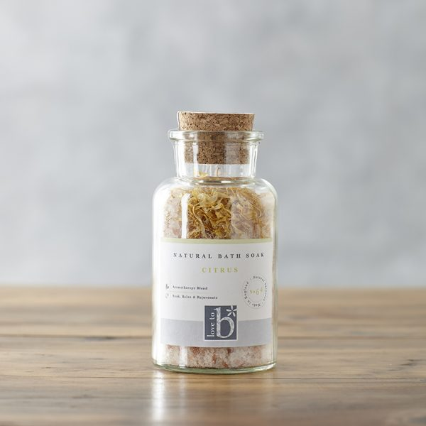 A glass bottle of natural citrus bath salts with a cork stopper and white label stood on a wooden surface