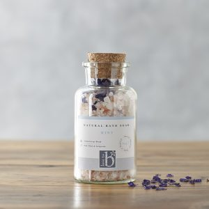 A glass bottle of natural mint bath salts with a cork stopper and white label stood on a wooden surface
