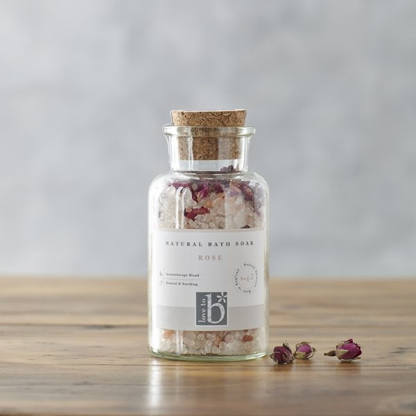 A glass bottle of natural rose bath salts with a cork stopper and white label stood on a wooden surface