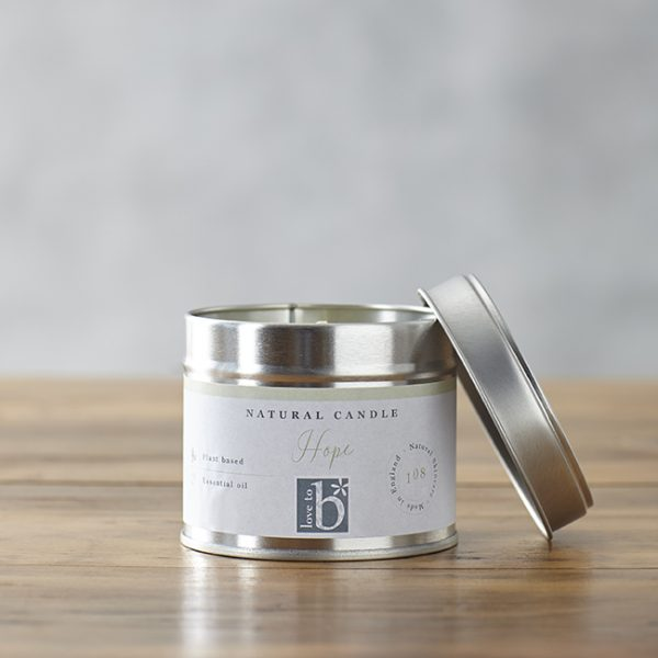 Natural soy wax candle 'Hope' in a silver metal tin with lid on a wooden surface with a grey background
