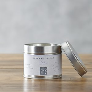 Natural soy wax candle 'Relax' in a metal tin with lid on a brown surface with a grey background