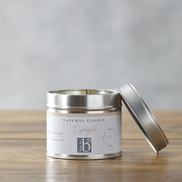 Natural soy wax candle 'Energise' in a silver metal tin with a lid on a brown surface with a grey background