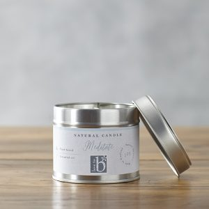 Natural soy wax candle 'meditate' in a metal tin on a wooden surface with a grey background