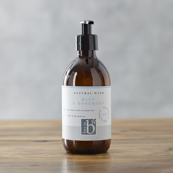 Natural mint and rosemary hand and body wash in an amber glass bottle with a white label on a wooden surface
