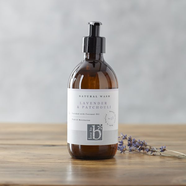 Natural Lavender hand and body wash in an amber glass bottle with a white label next to some sprigs of lavender on a wooden surface