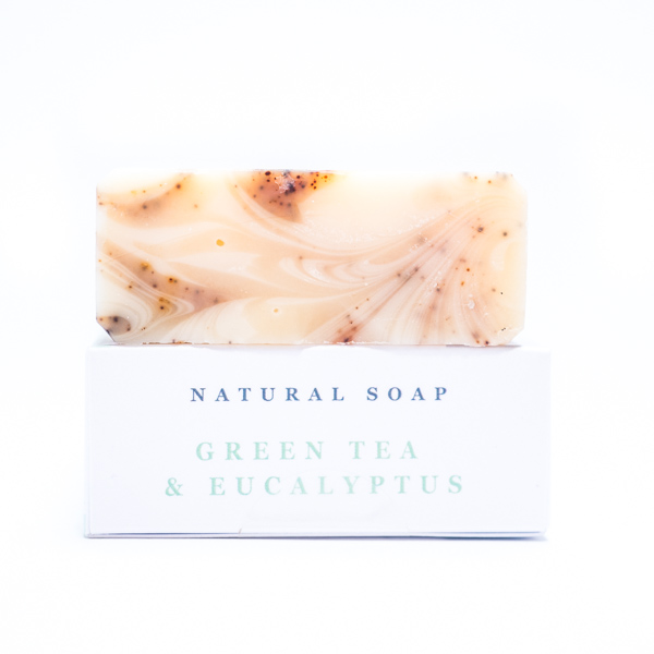 Cream and brown swirled Natural green tea and eucalyptus soap on top of its white rectangular box with a white background