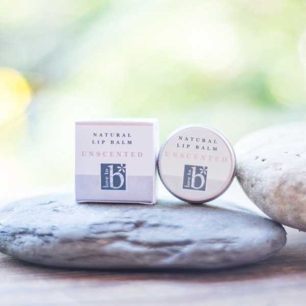 Natural unscented lip balm in a metal circular tin next to its white square box on a rock in front of a green background