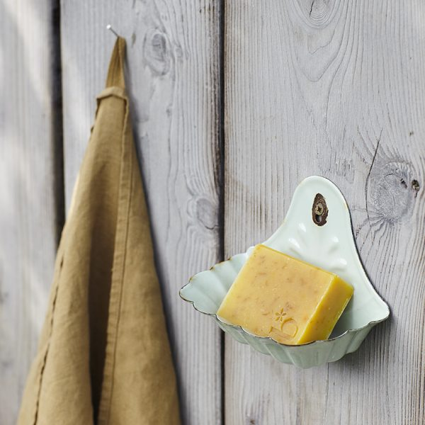 A chamomile and callendula natural soap in a pale green wall hung soap dish next to a brown towel