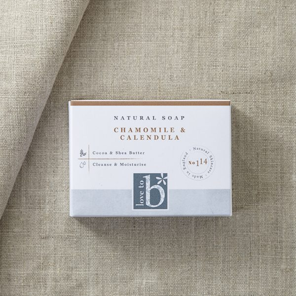 White rectangular natural soap packaging laid on a material background