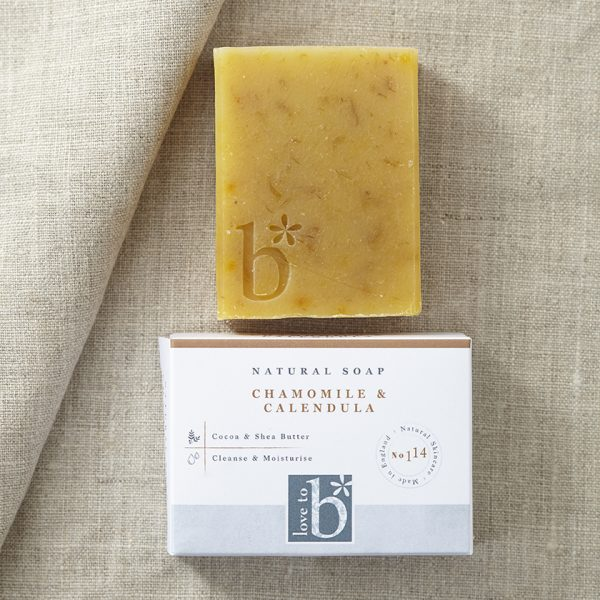 Dark yellow chamomile and Callendula natural soap laying on a background of beige material above white rectangular box