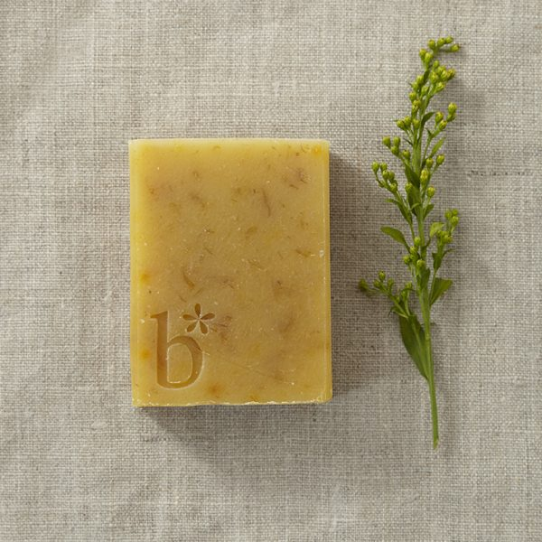 A chamomile and callendula natural soap laid on a brown material next to a stem of leaves