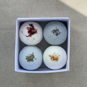 Four natural bath bombs, cedarwood and lemongrass, citrus, rose and lavender nestled in a square white cardboard box on a linen background