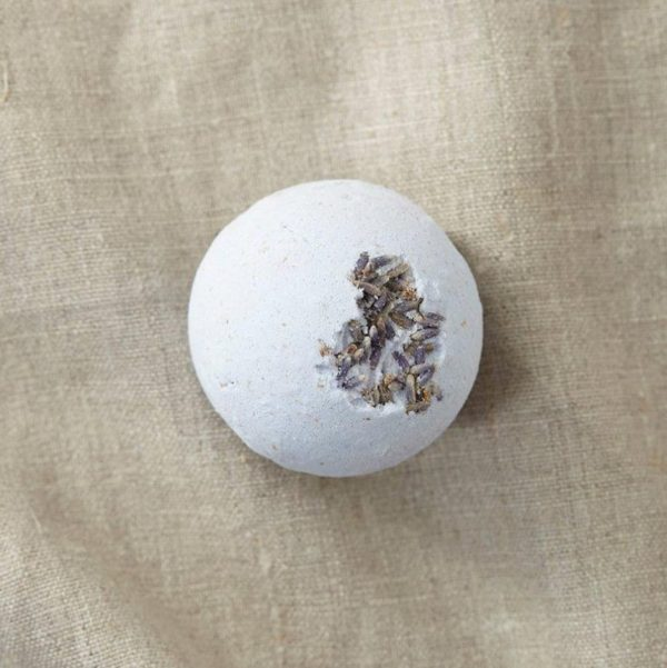 A lilac lavender bath bomb with lavender buds on a brown material background