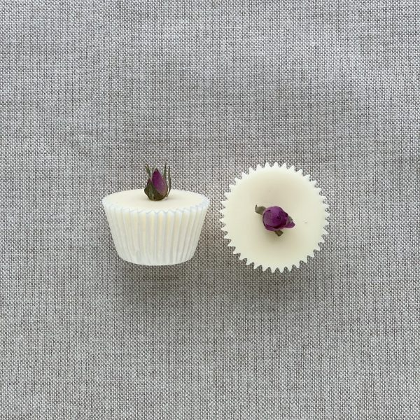 Two natural rose bath melts in paper cases. One lying on its side and one where you can see the top. Both are topped with a single rose bud. On a linen background