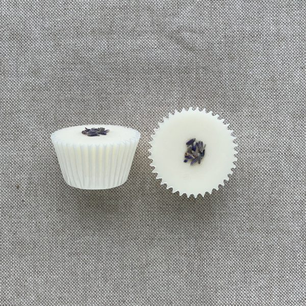 Two white natural lavender bath melts in paper cases topped with lavender buds on a linen background