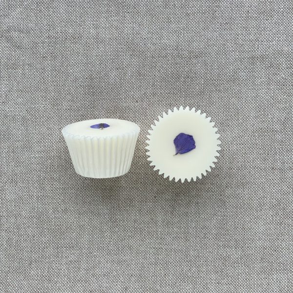 Two cream natural mint bath melts in paper cases topped with a delphinium petal and with a linen background
