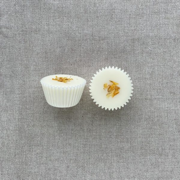 Two cream natural citrus bath melts in paper cases topped with calendula petals on a linen background