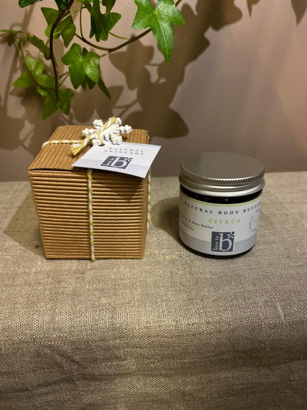 Natural citrus body butter next to its brown cardboard gift box with yellow and white string bow