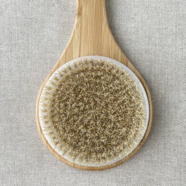 Natural wooden long handled back brush with natural bristles on a linen background