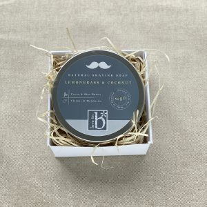 Natural shaving soap in a tin with the lid on in a white cardboard box, nestled in wood wool on a linen background