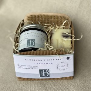Gardeners gift set in a cardboard box showing a wooden nail brush, lavender hand balm and lavender and patchouli soap nestled in wood wool on a linen background