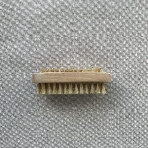 Natural wooden shaving brush with natural bristles on a linen background