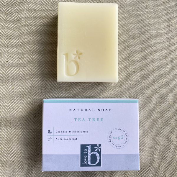 Cream natural tea tree soap above its white rectangular box on a linen background
