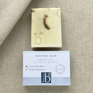 Cream Green tea, eucalyptus and lemongrass soap with brown swirls above its white rectangular box on a linen background