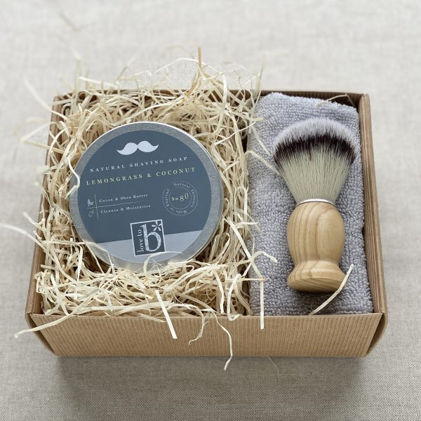 Natural shaving gift set in a cardboard box showing a shaving soap in a tin, wooden shaving brush and flannel nestled in wood wool.