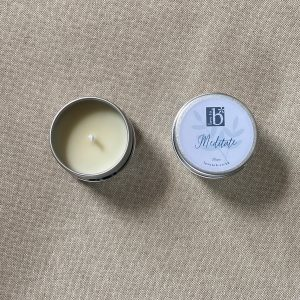 Mini natural soy wax candle 'meditate' in a metal tin with a lid on a brown material background
