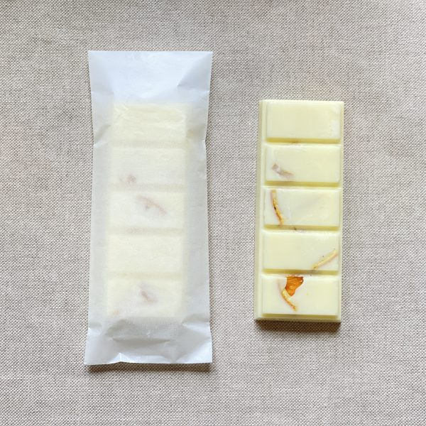 white energise natural soy wax melt snap bar with dried orange peices in its glassine bag package next to a non-packaged one on a brown material background