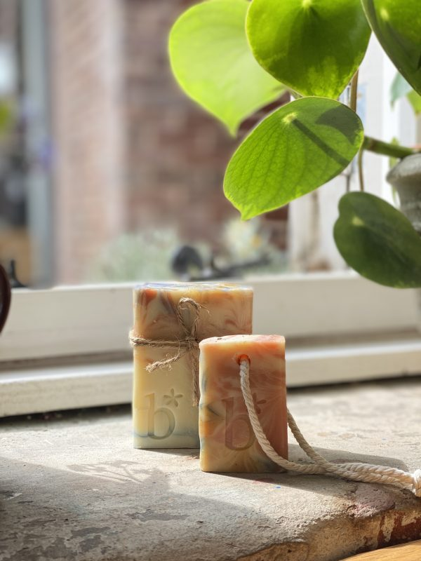 Tutti frutti half bar soap on a rope in front of a full sized bar tutti frutti on a stone surface in front of an open window