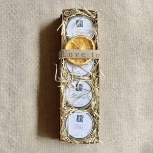 Box of four mini natural aromatherapy candles in a brown cardboard box with wood wool on a brown material background