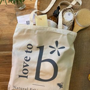 A natural cotton tote bag with the Love to b logo printed in grey filled with Love to b products and lying on a wooden surface
