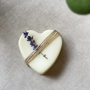 White natural lavender heart soap with twine wrapped around it and a sprig of lavender tucked in. Sitting on a background of linen.